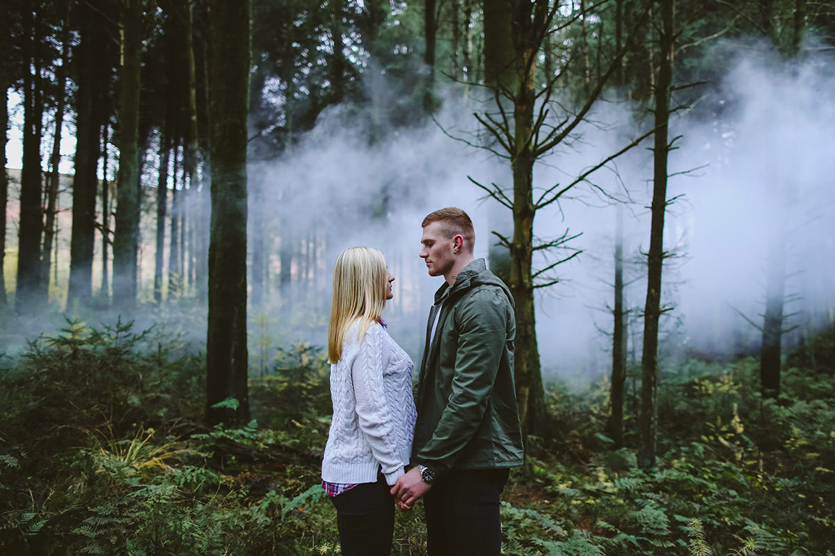 engagment session in trees with smoke near winter hill in bolton