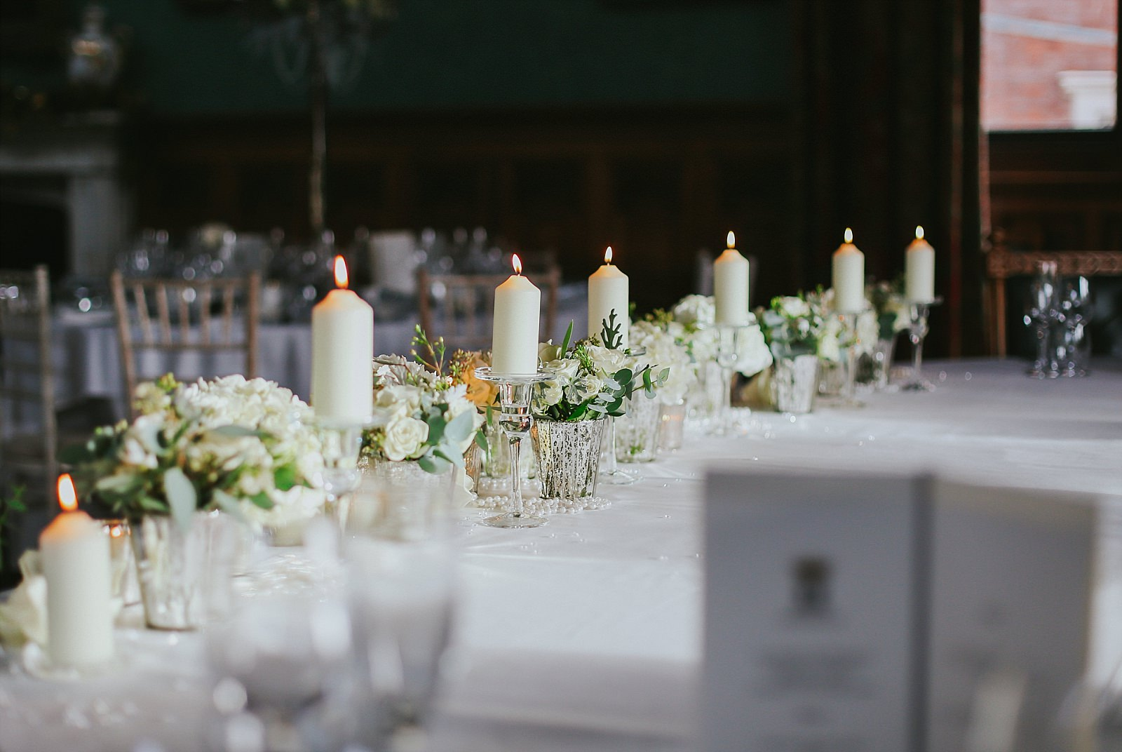 candles and flowers on a table at a wedding