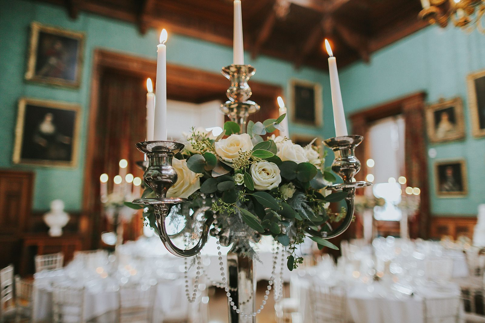 candelabra decorated with white roses and winter ferns