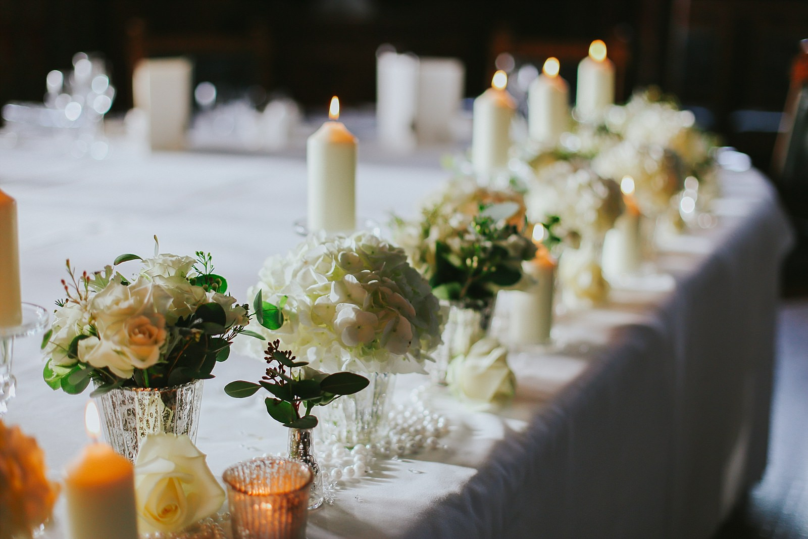 Candles and Hydrangea's on a wedding top table by embee photography