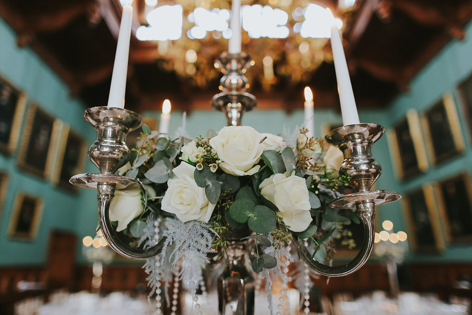 Whte roses arranged on a candelabra top in a large room
