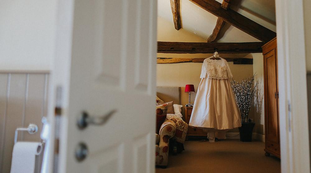 boho style wedding dress hung up in cottage