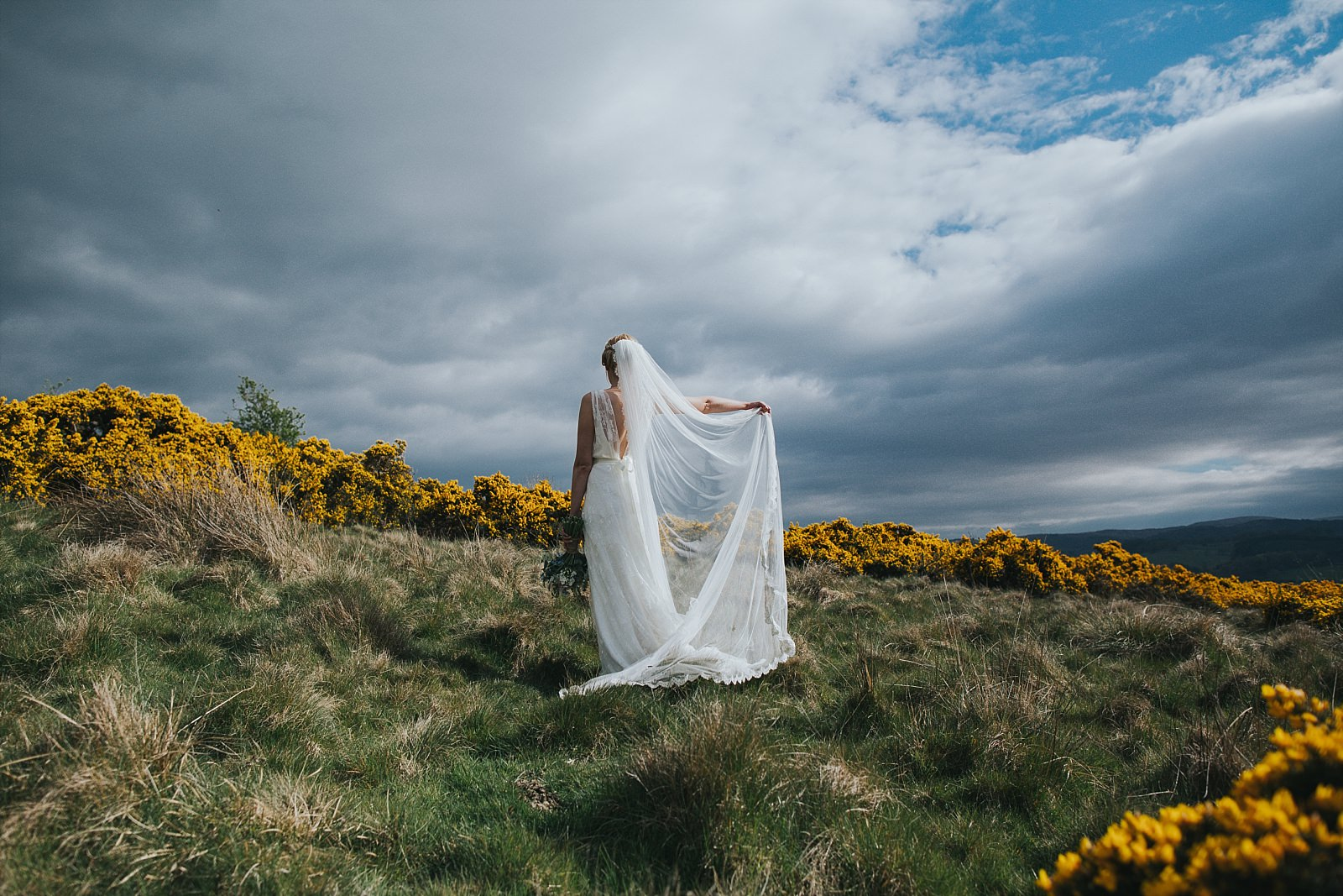 bride lifting dress up amongst gorse bushes with dramatic landscape