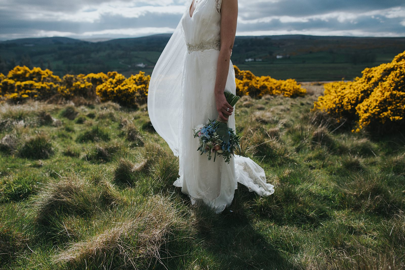 bride with bouquet in the gorse bushes at knipe hall