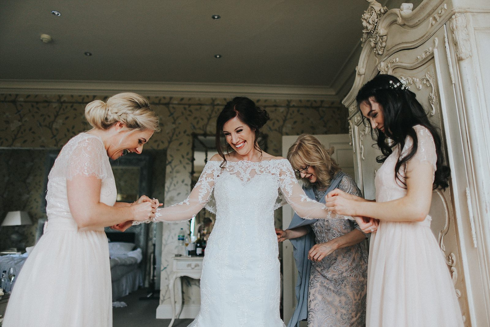 fun wedding photographer captures the bridesmaids helping