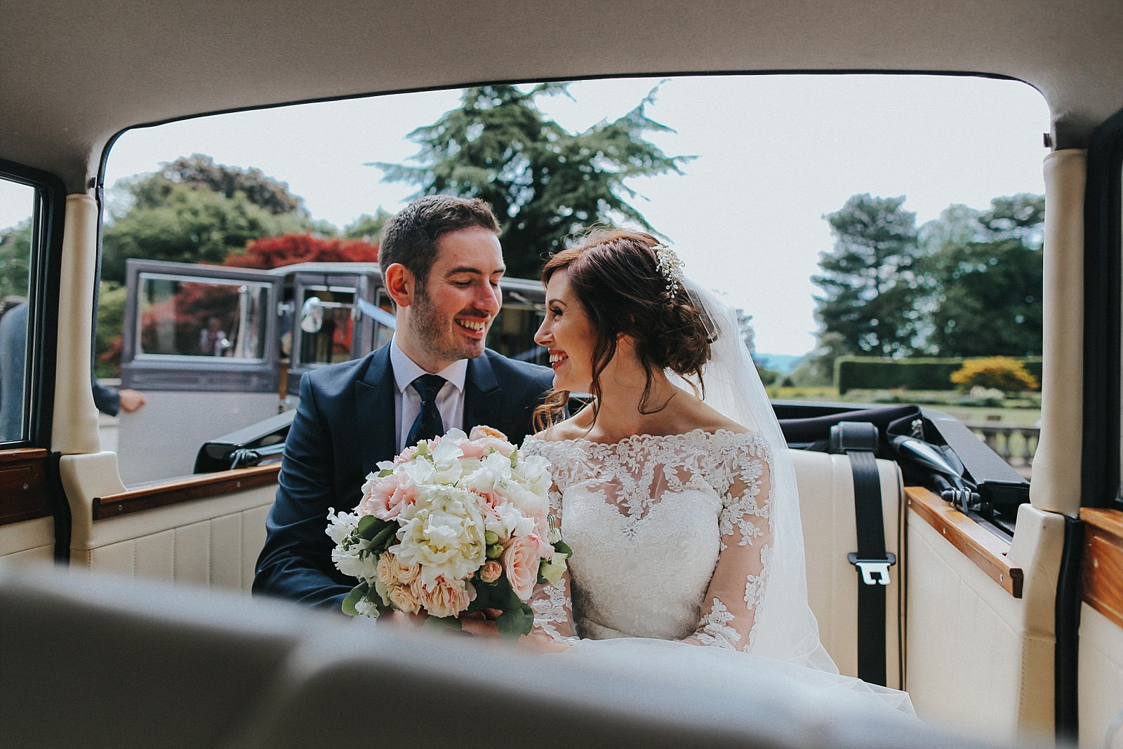 bride and groom smile in their malvern wedding car