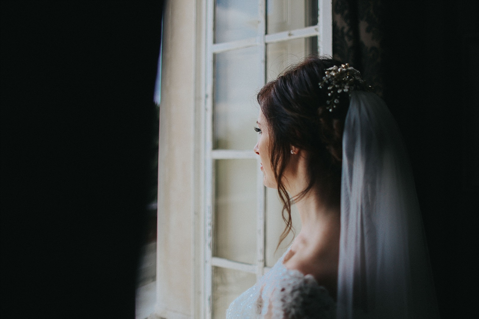bride looking out the bridal suite at eaves hall
