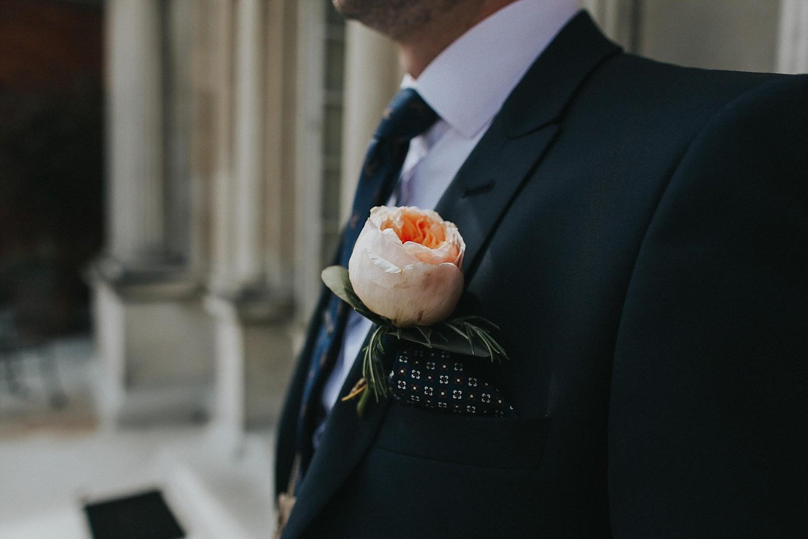 groom wears hius peony buttonhole