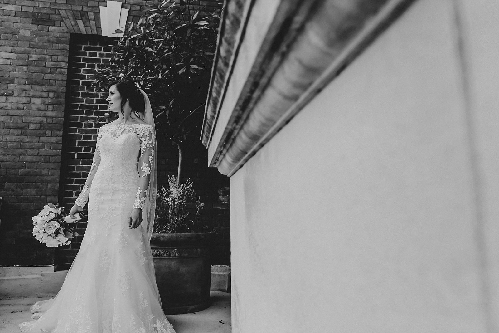 bride stands with her bouquet at eaves hall