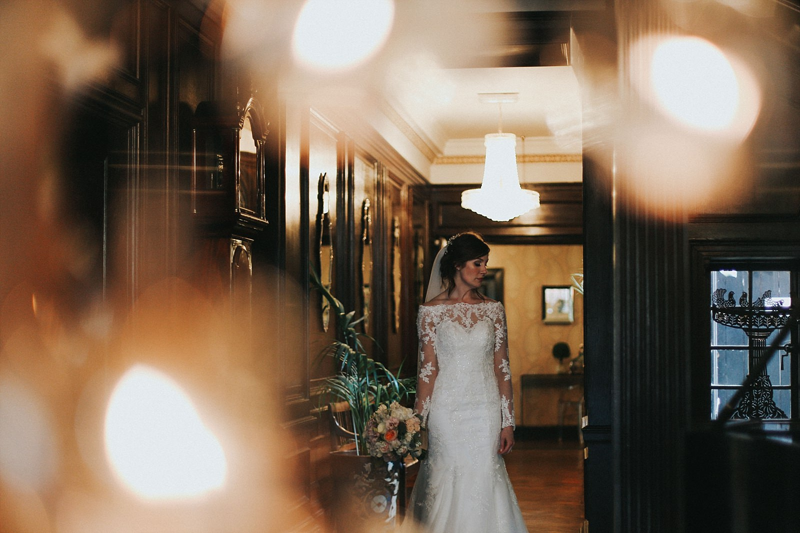 eaves hall wedding photographer captures the bride walking down the corridor