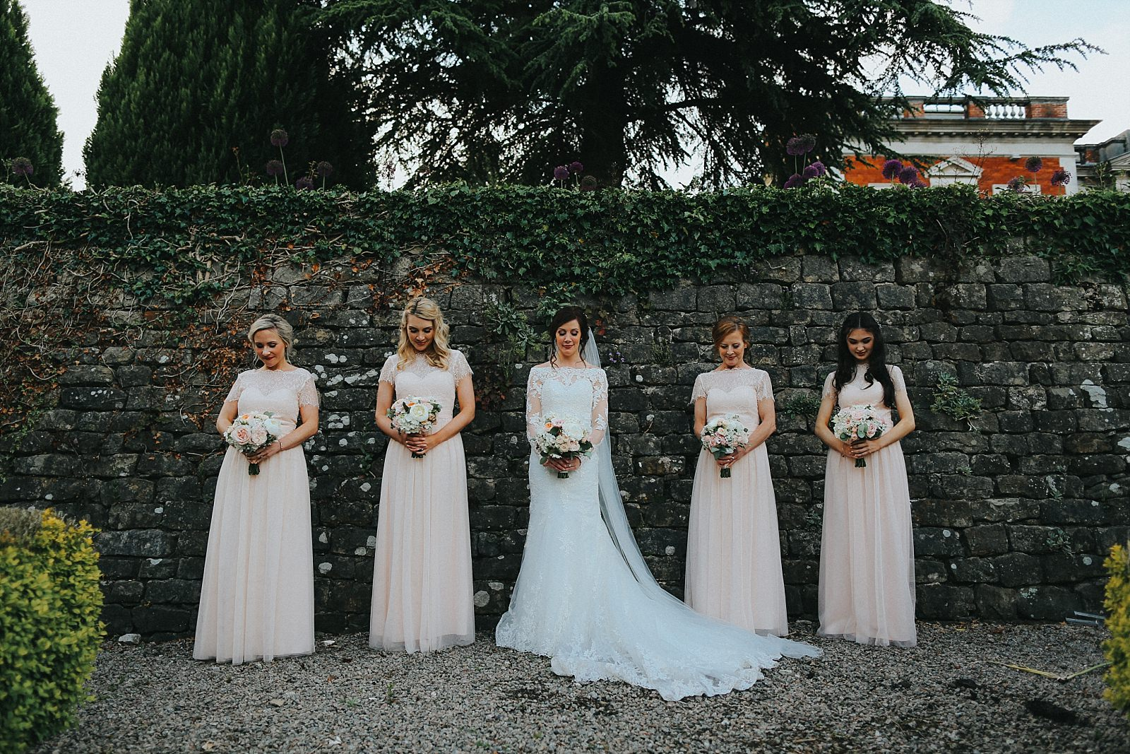bridemaids in a line looking down with their bouquets