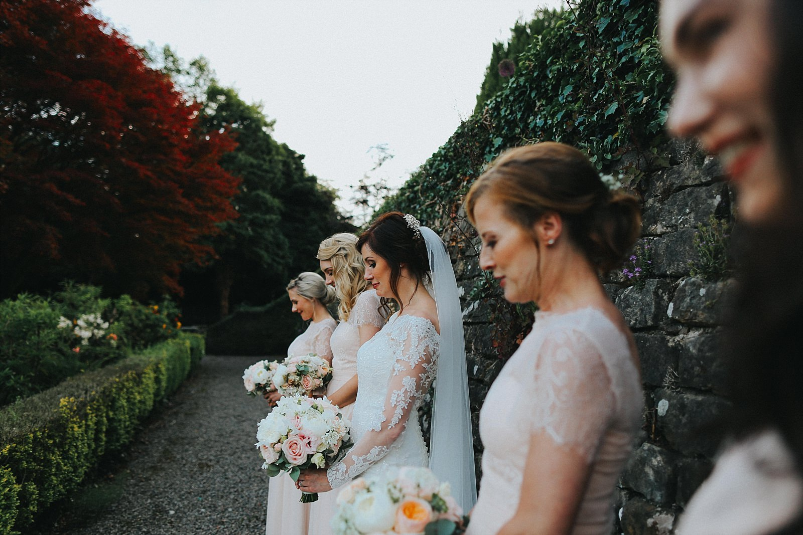 bride and bridesmaids lean against a wall at eaves hall