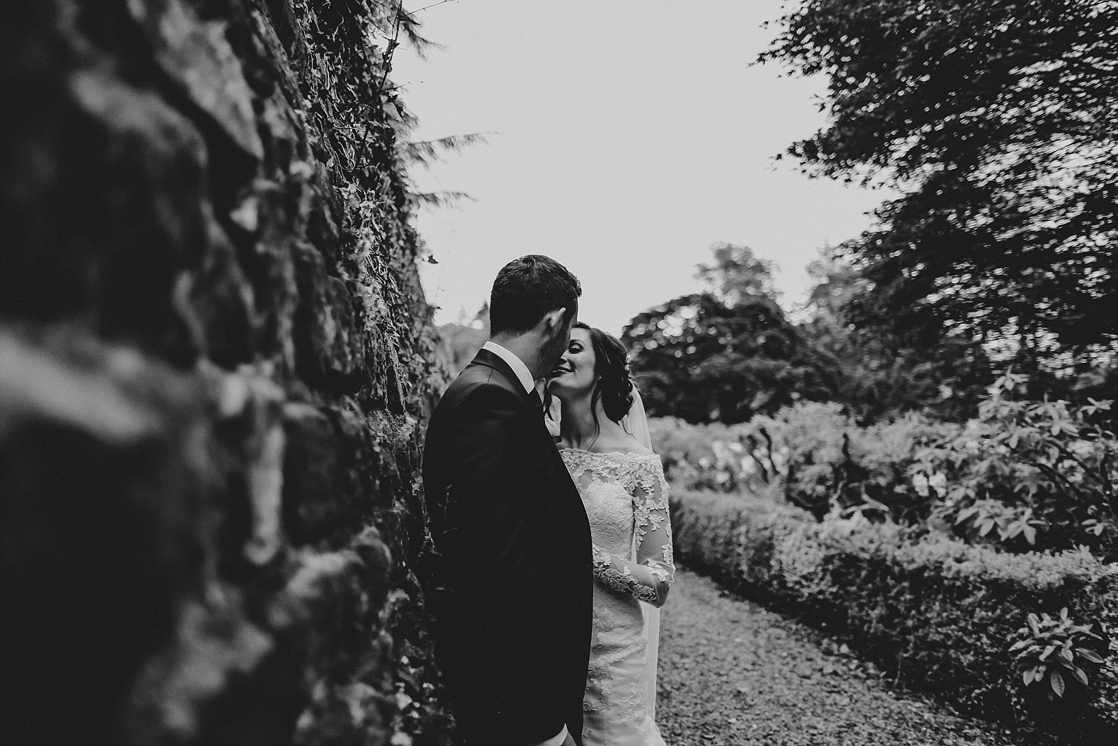 bride and groom kissing in eaves hall grounds