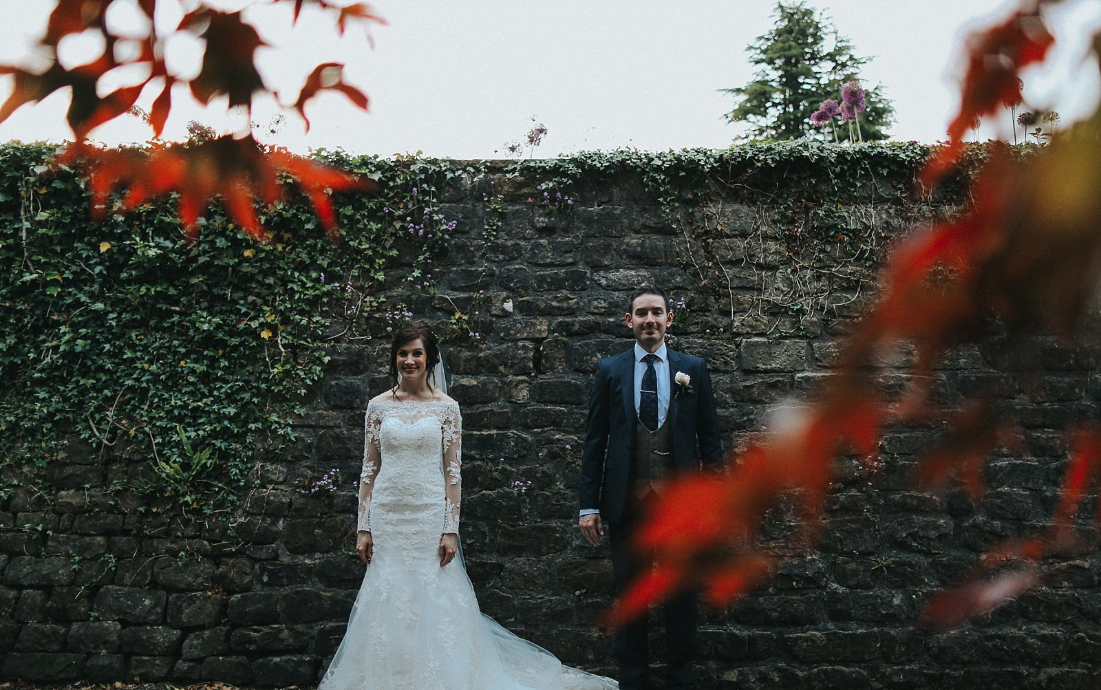 bride and groom pose against a brick wall