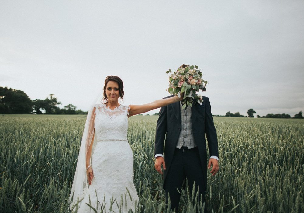 bride has fun with groom in field