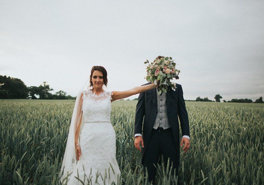 bride has fun with groom in field