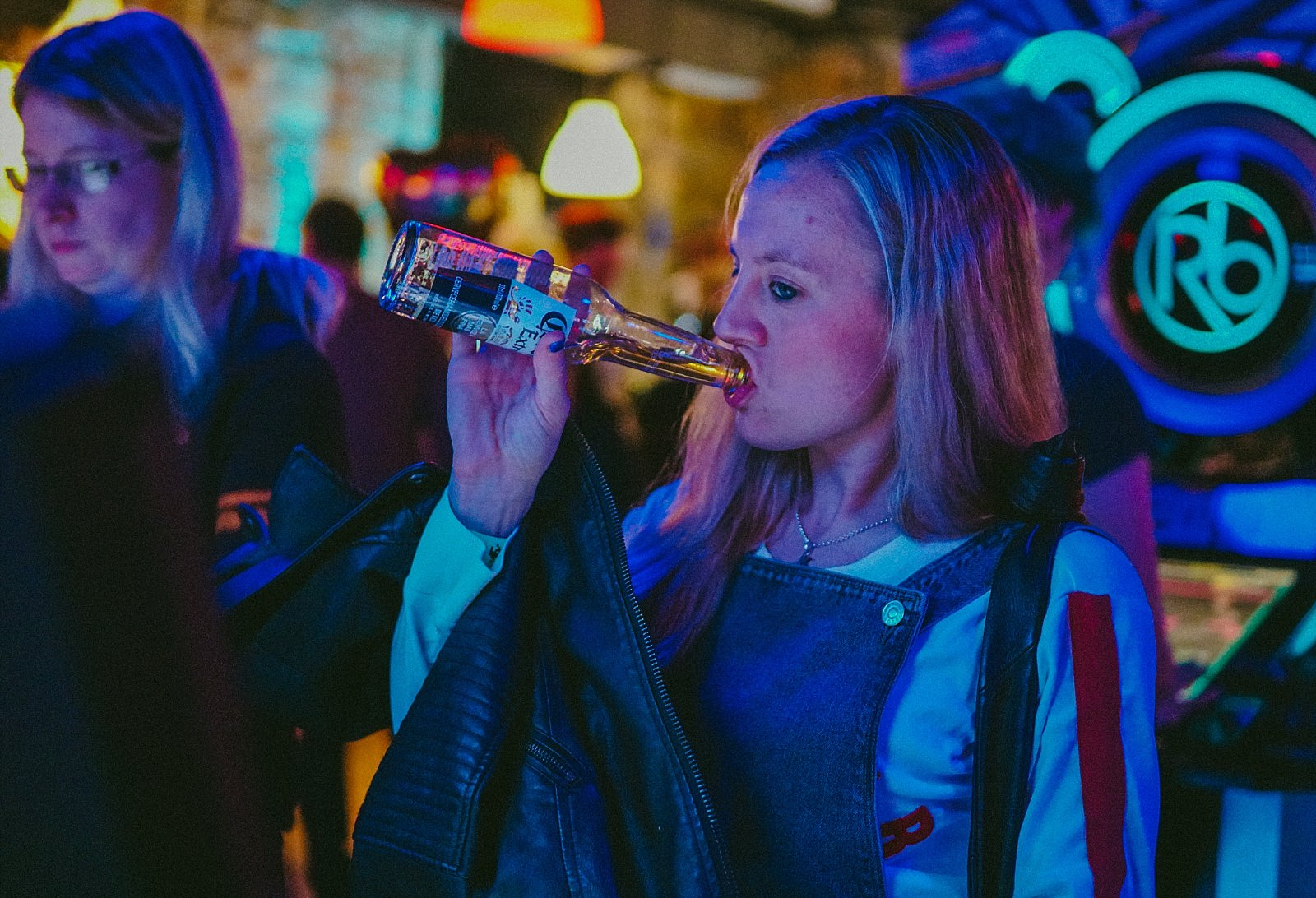 girl drinking corona in an arcade with games