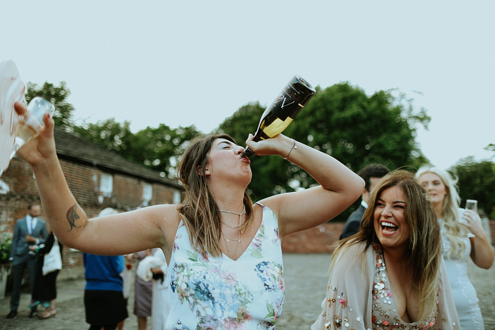 insane wedding guest drinking champagne out of bottle