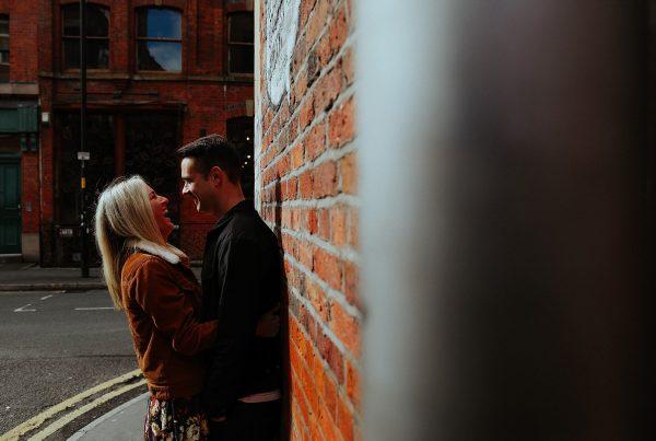 laughing boy and girl along a brick wall