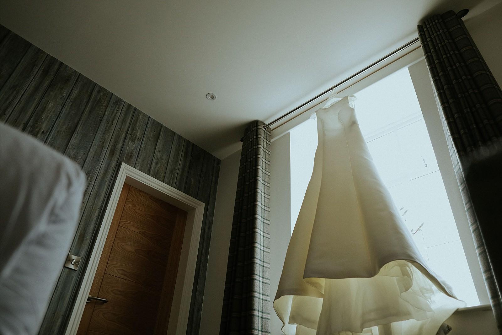 Pronovias white wedding dress infront of window