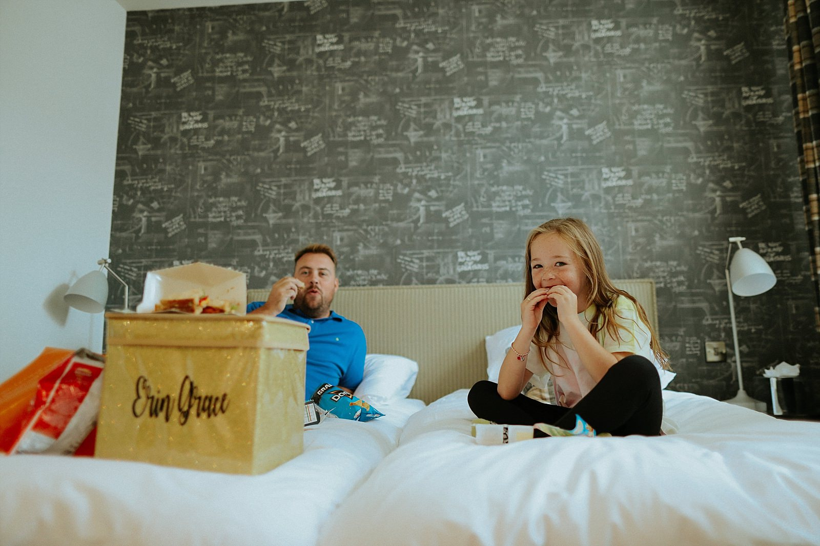 Girl on bed eating a sandwich
