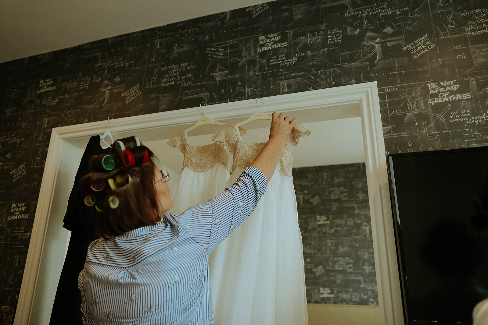 brides mum hanging up bridesmaids dresses