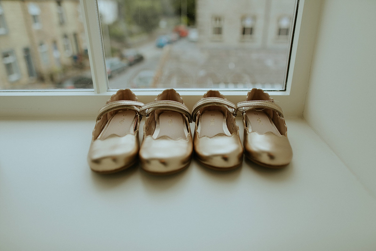 gold bridesmaids shoes on a window ledge