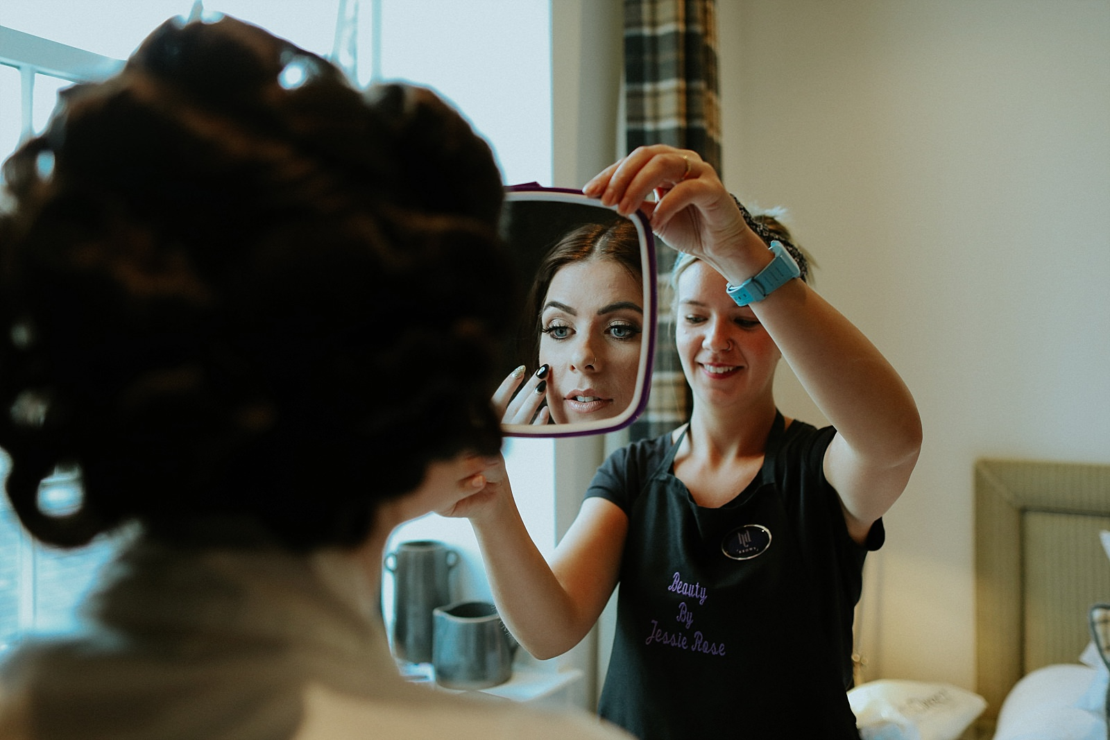 bride looking at her self in a mirror with her make up artist