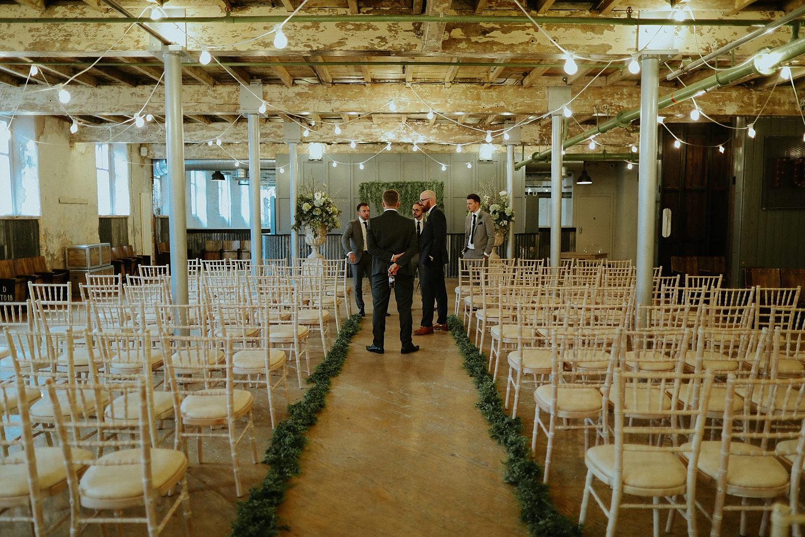 grooms stood at the top of the aisle.
