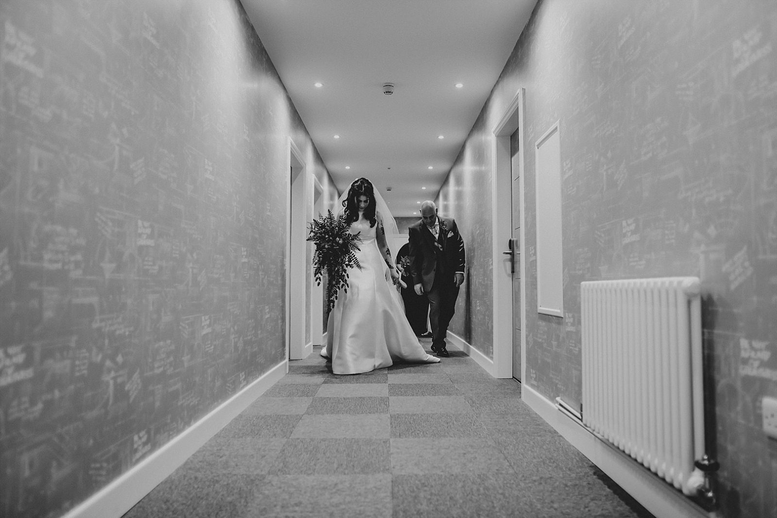 bride walking to the the ceremony room at holmes mill wedding venue