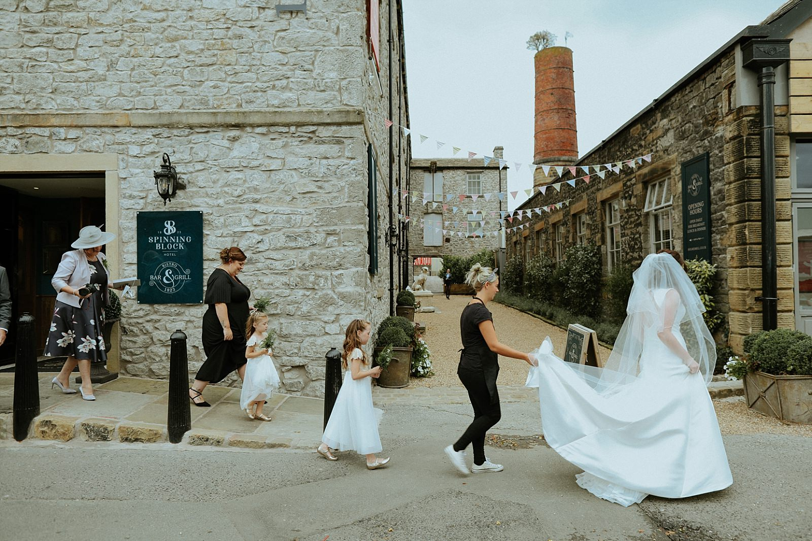 bride walking in to holes mill with the bridal party following her