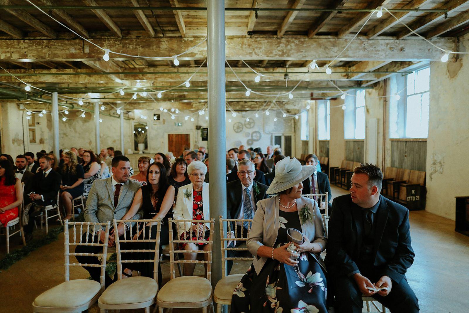 wedding guests in holmes mill industrial wedding venue