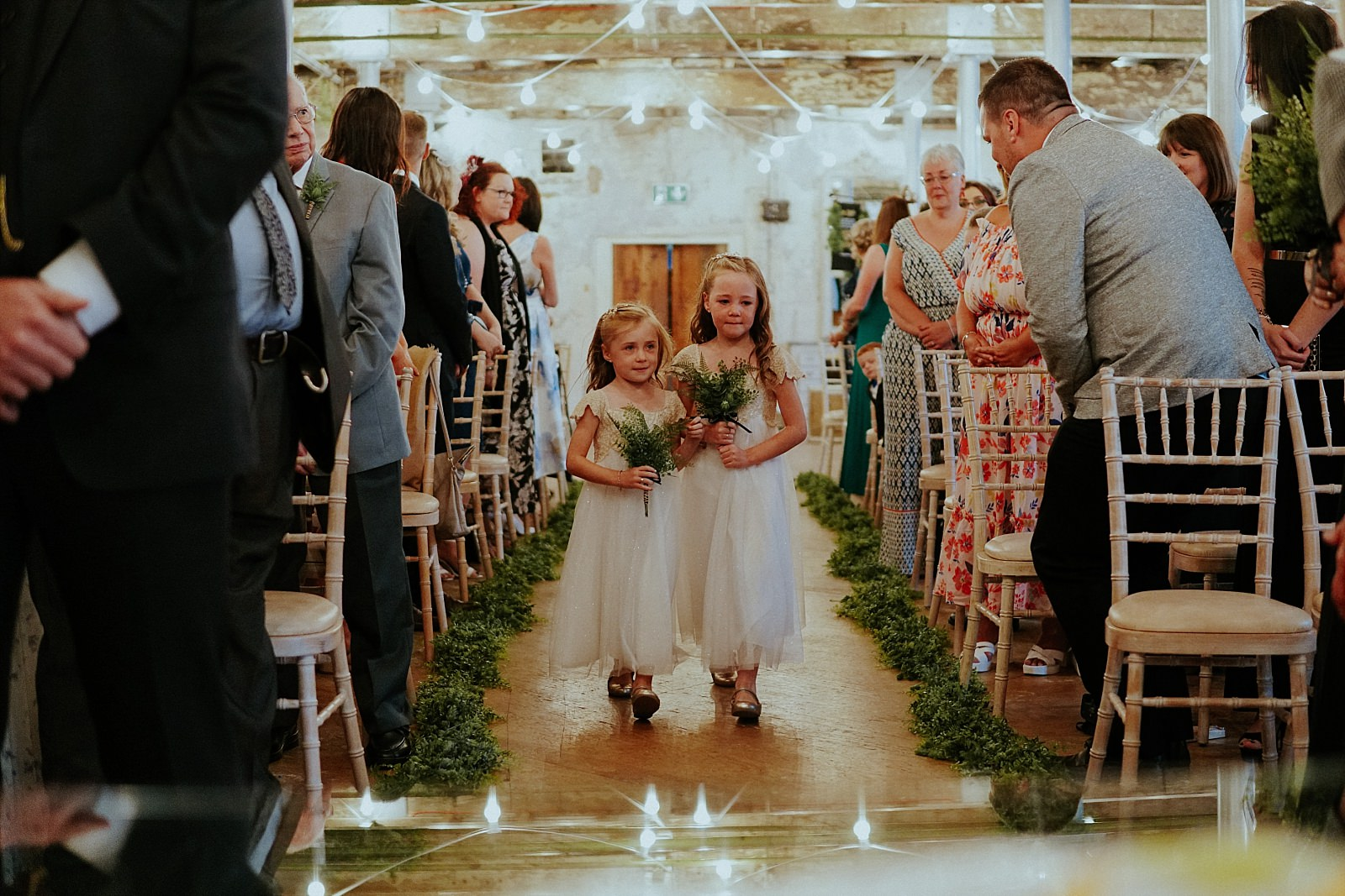 cute bridesmaids in white dresses walking down the aisle with green flowers