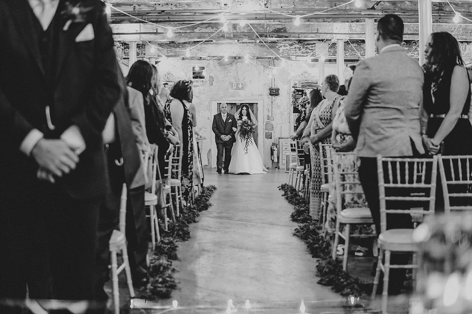 Bride walking into the ceremony room at Holmes Mill wedding venue