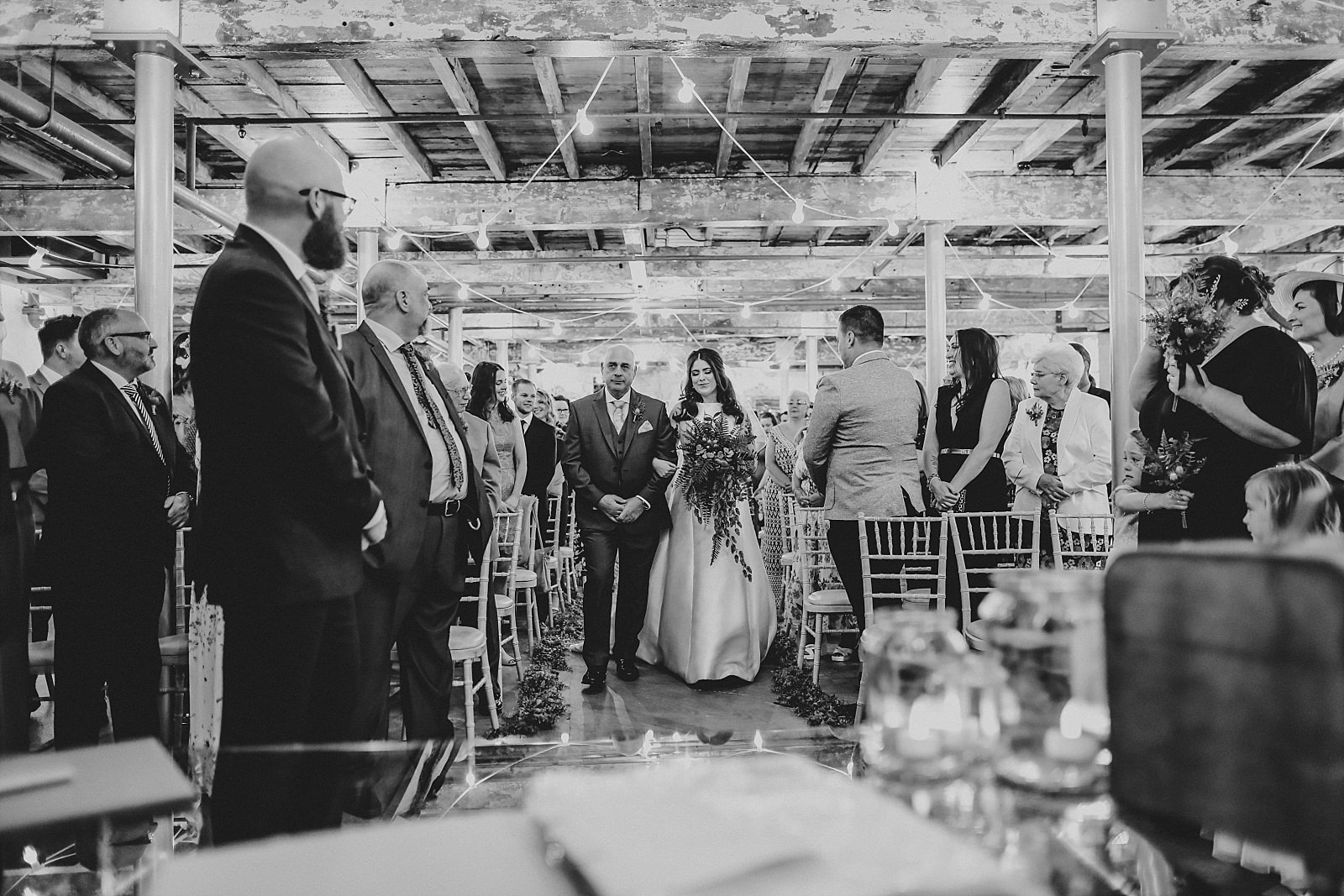 Industrial Ceremony as the bride walks own the aisle at Holmes mill