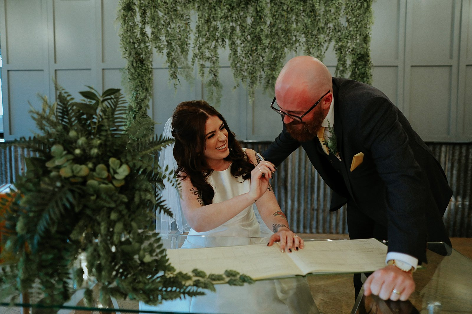 bride and groom laugh whilst signing the register
