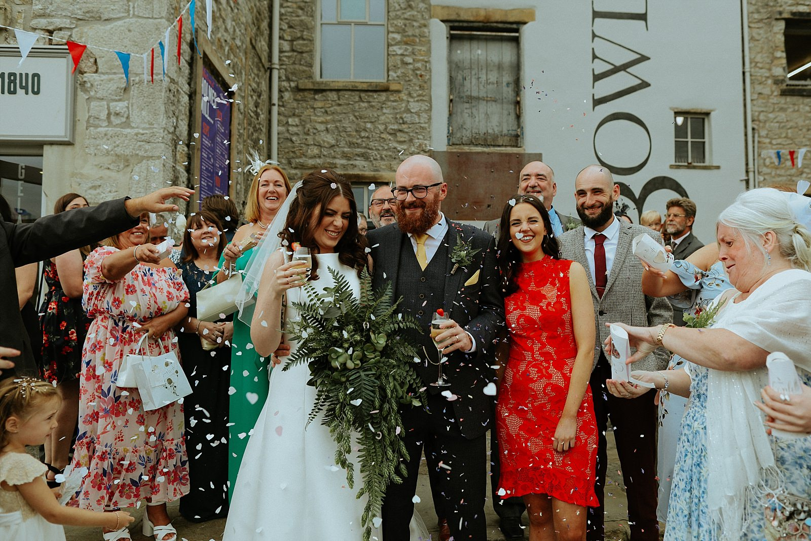 Bride and groom walk out of the Engine room and showered with confetti outside.