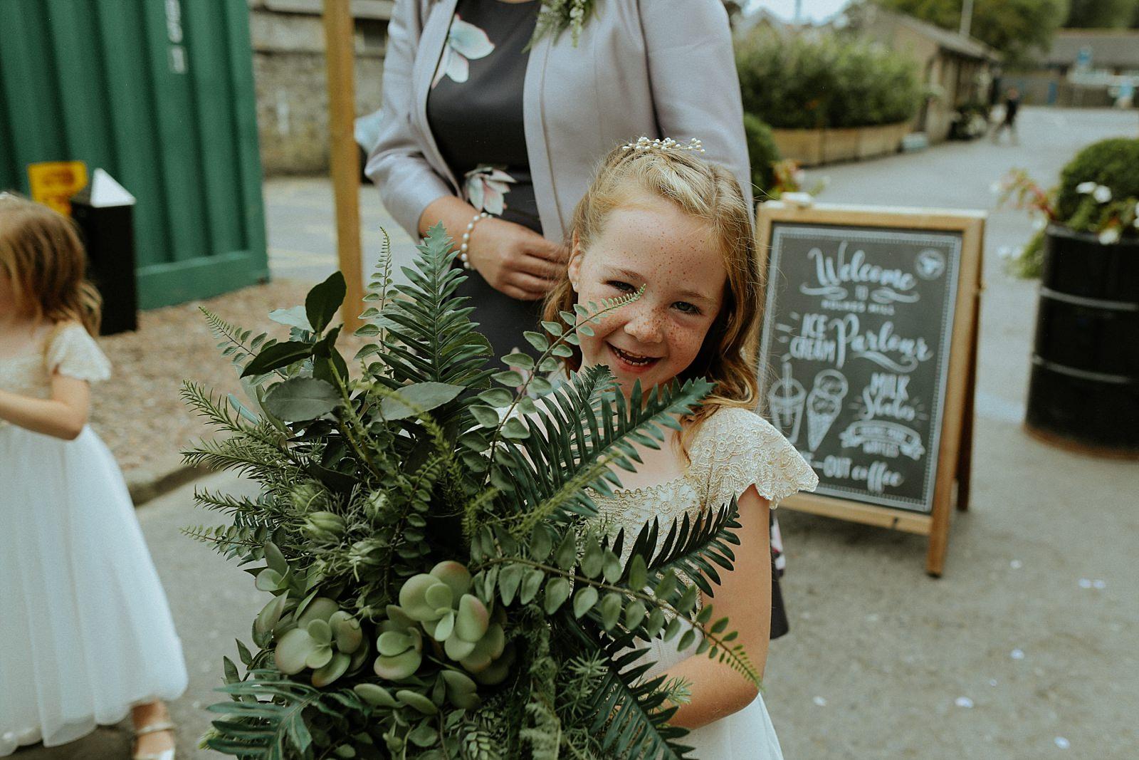 girl holding wild green wedding flowers