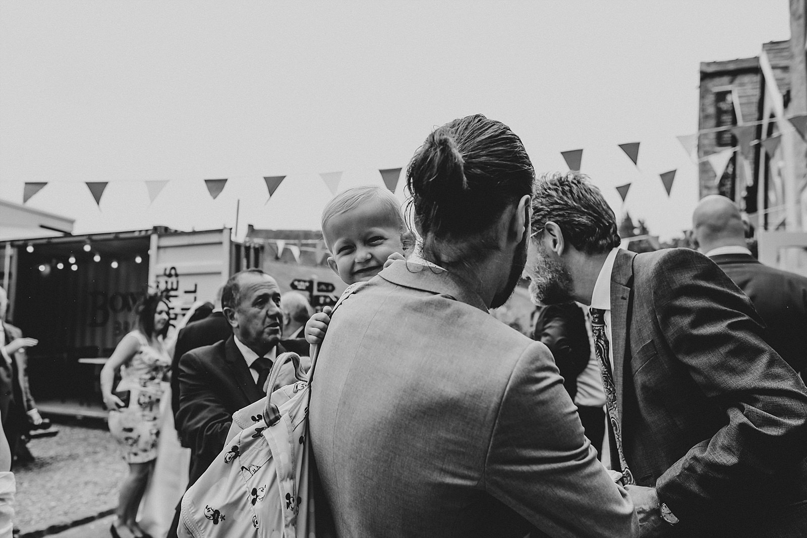cheeky boy smiling at wedding photographer