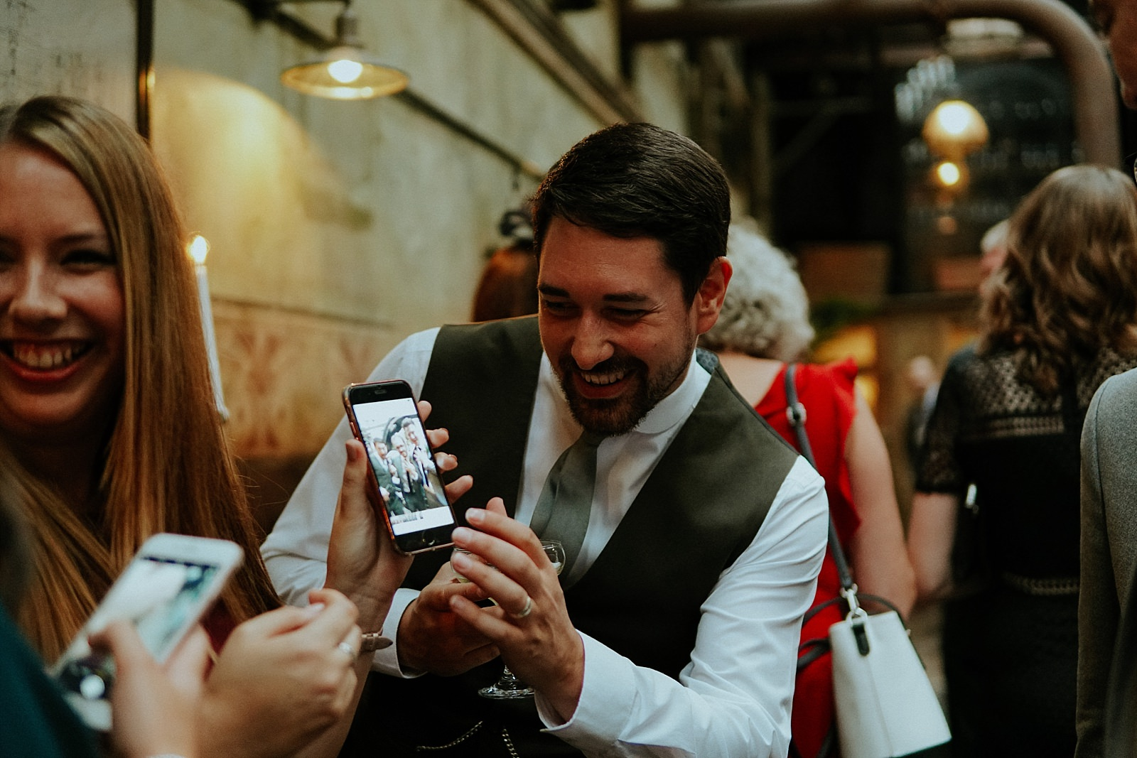 man laughing whilst playing on phone at a wedding