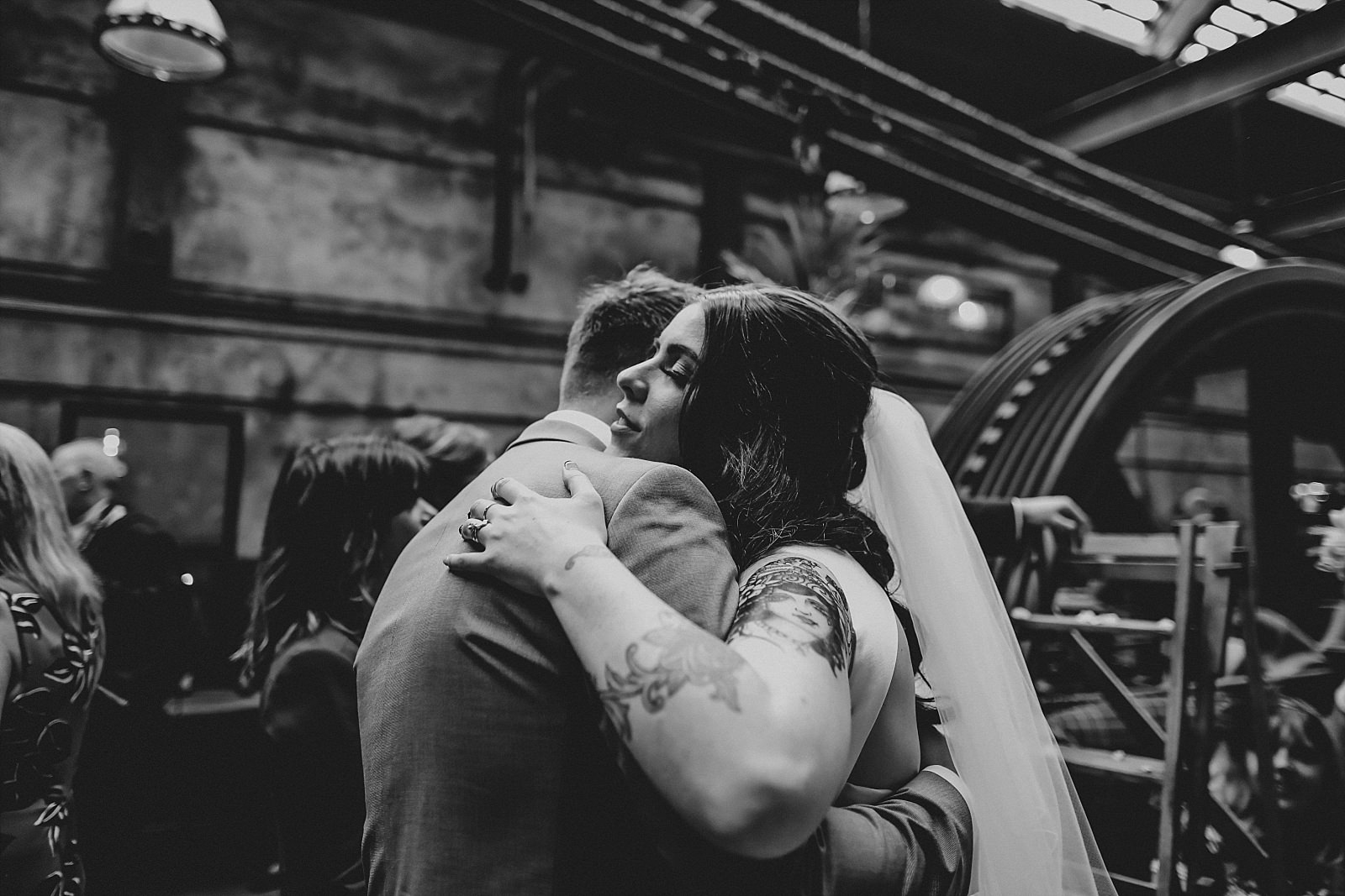 bride hugging guests in the engine room holmes mill