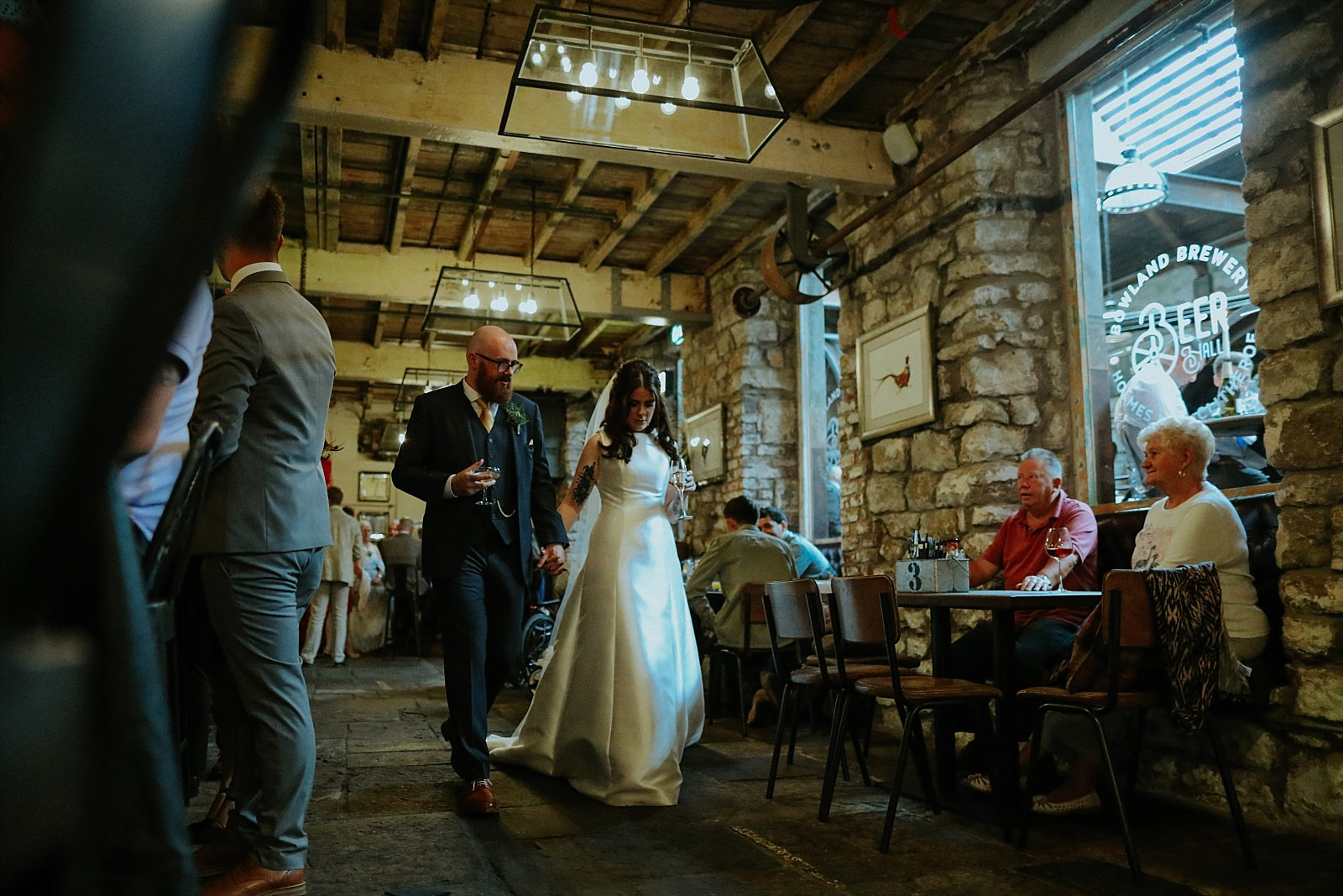 bride and groom walking through the beer hall in holmes mill