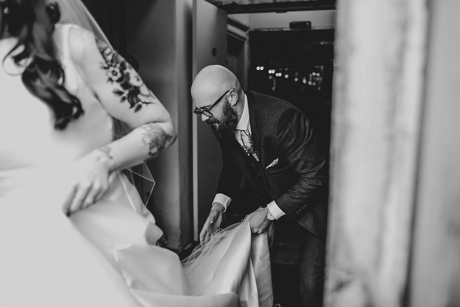 groom lifting up brides dress