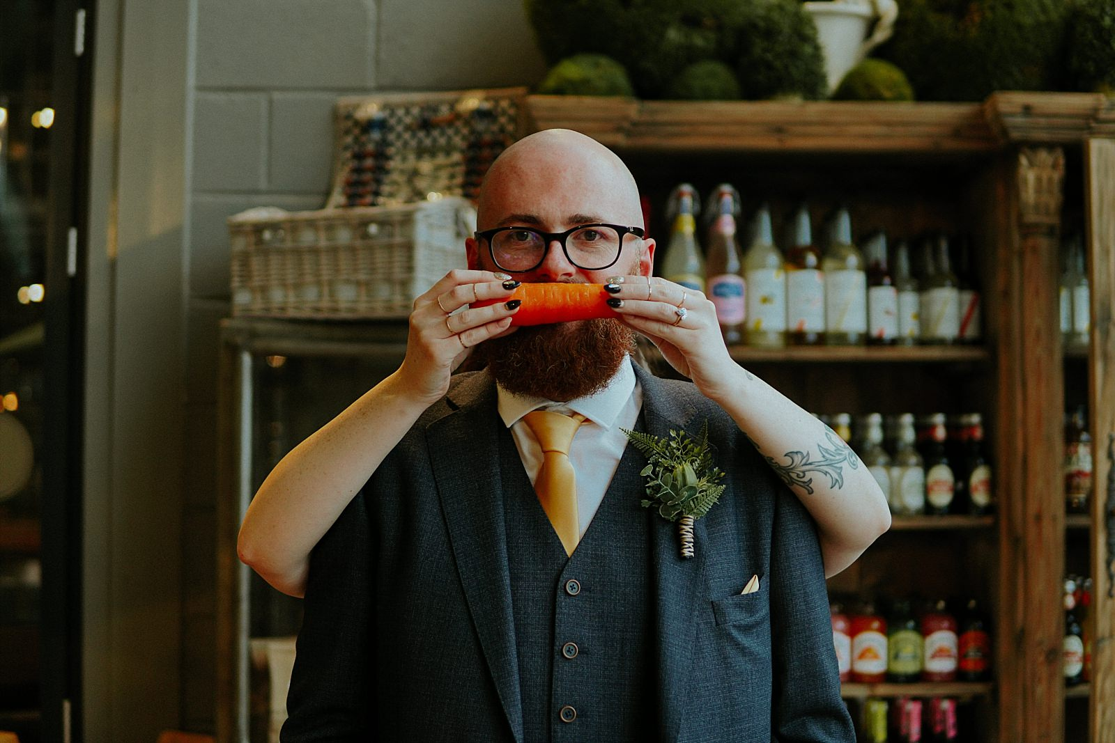 alternative wedding photographer and groom with carrot across his mouth
