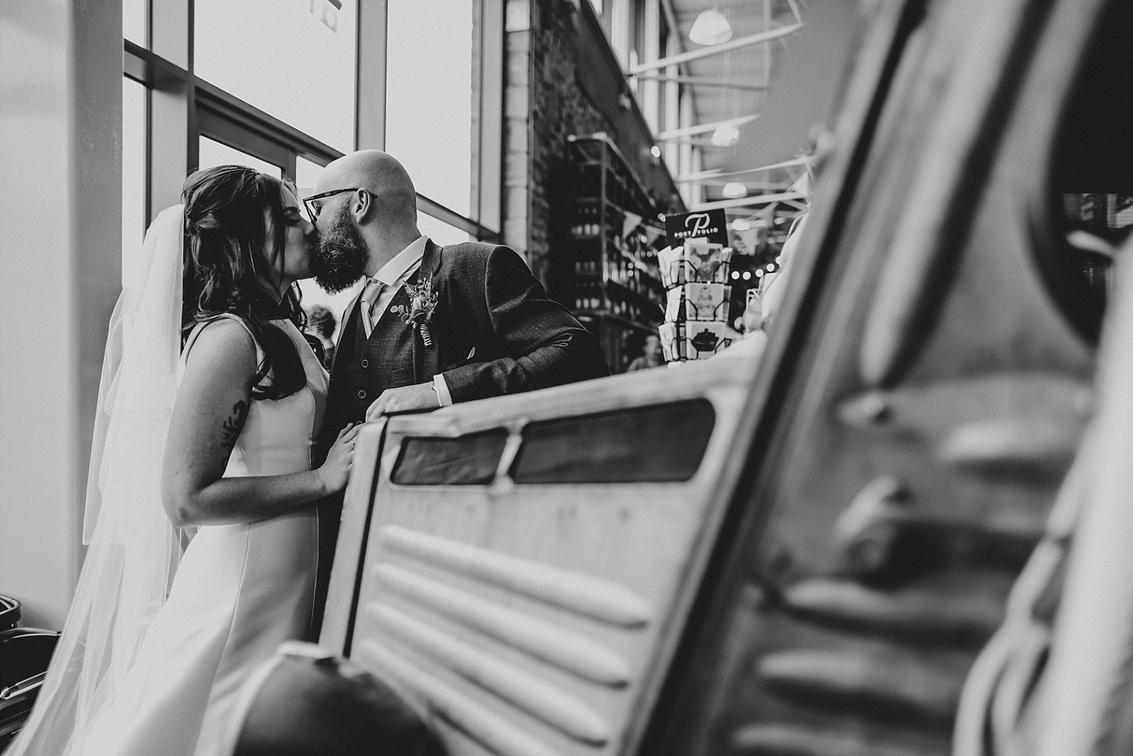 kissing bride and groom against vintage food truck