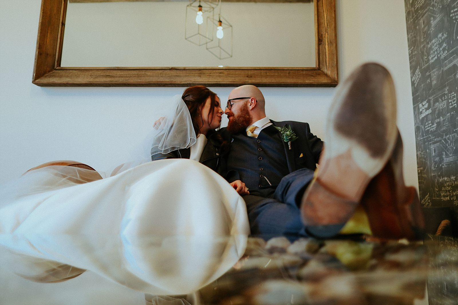 bride and groom nose to nose sat down on a chair