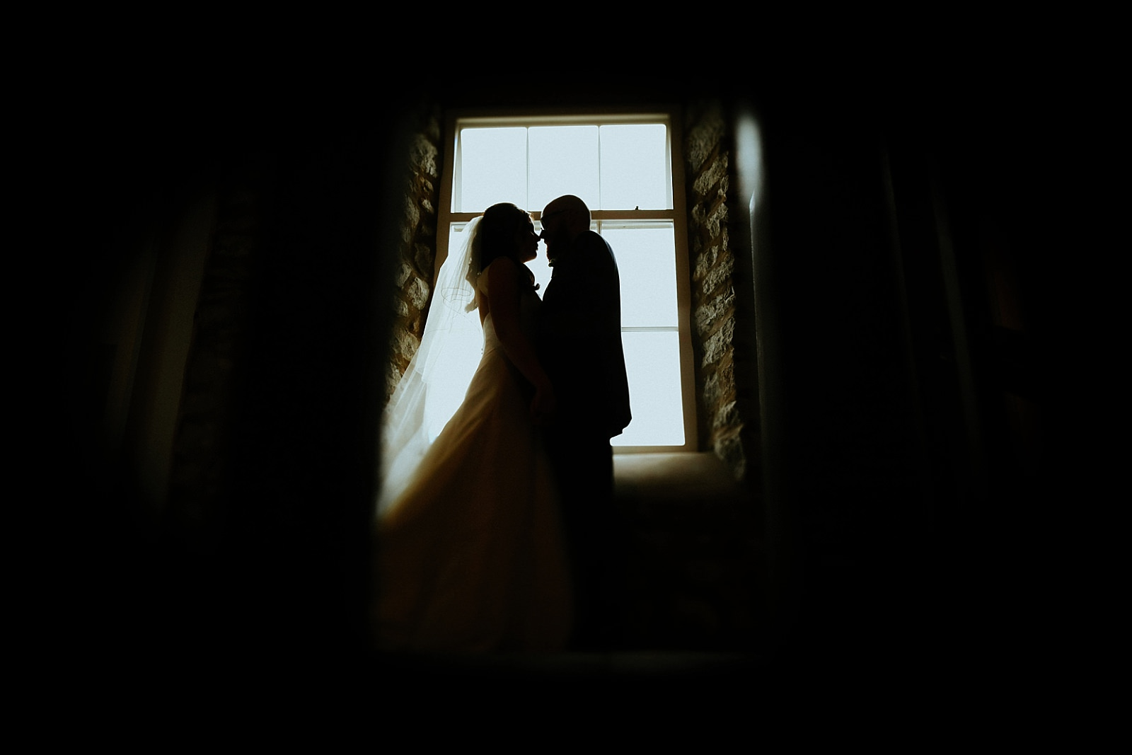 artistic shot of bride and groom by a window