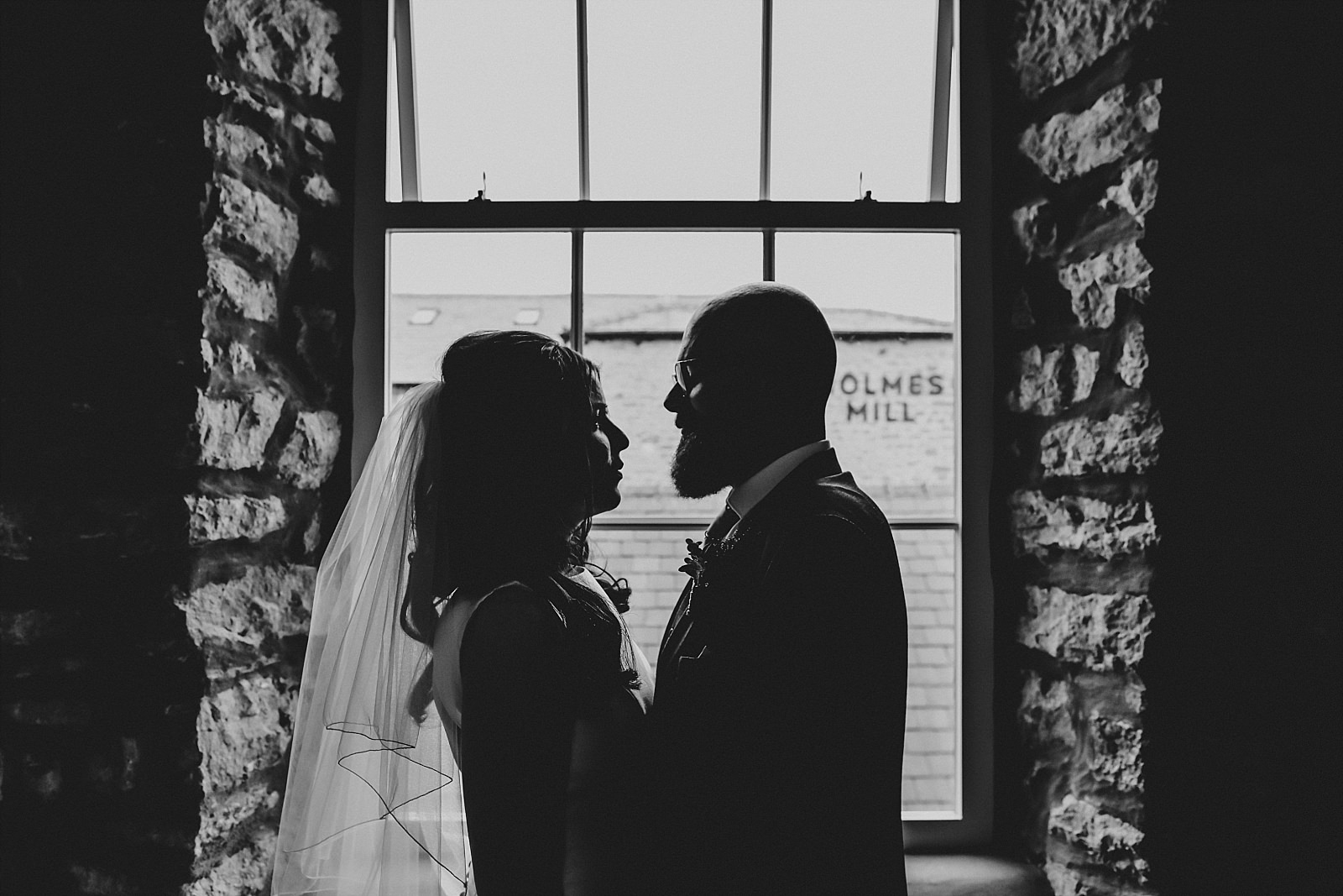 bride and groom getting close by a window