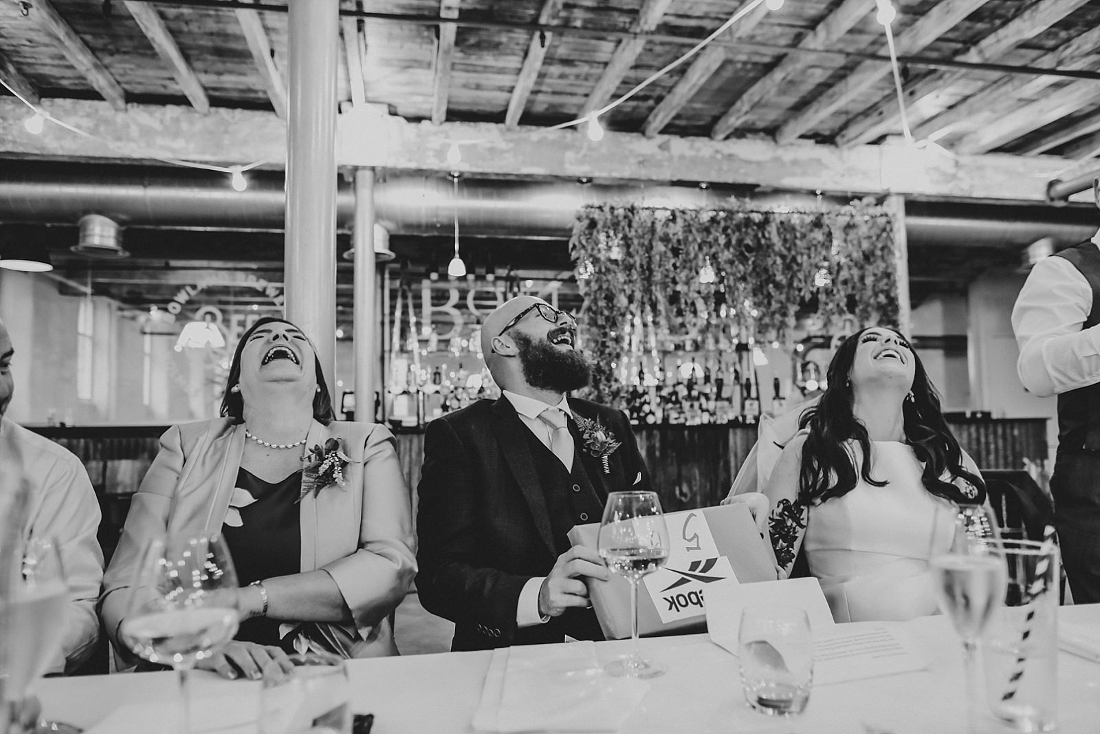 laughing bride and groom during speeches