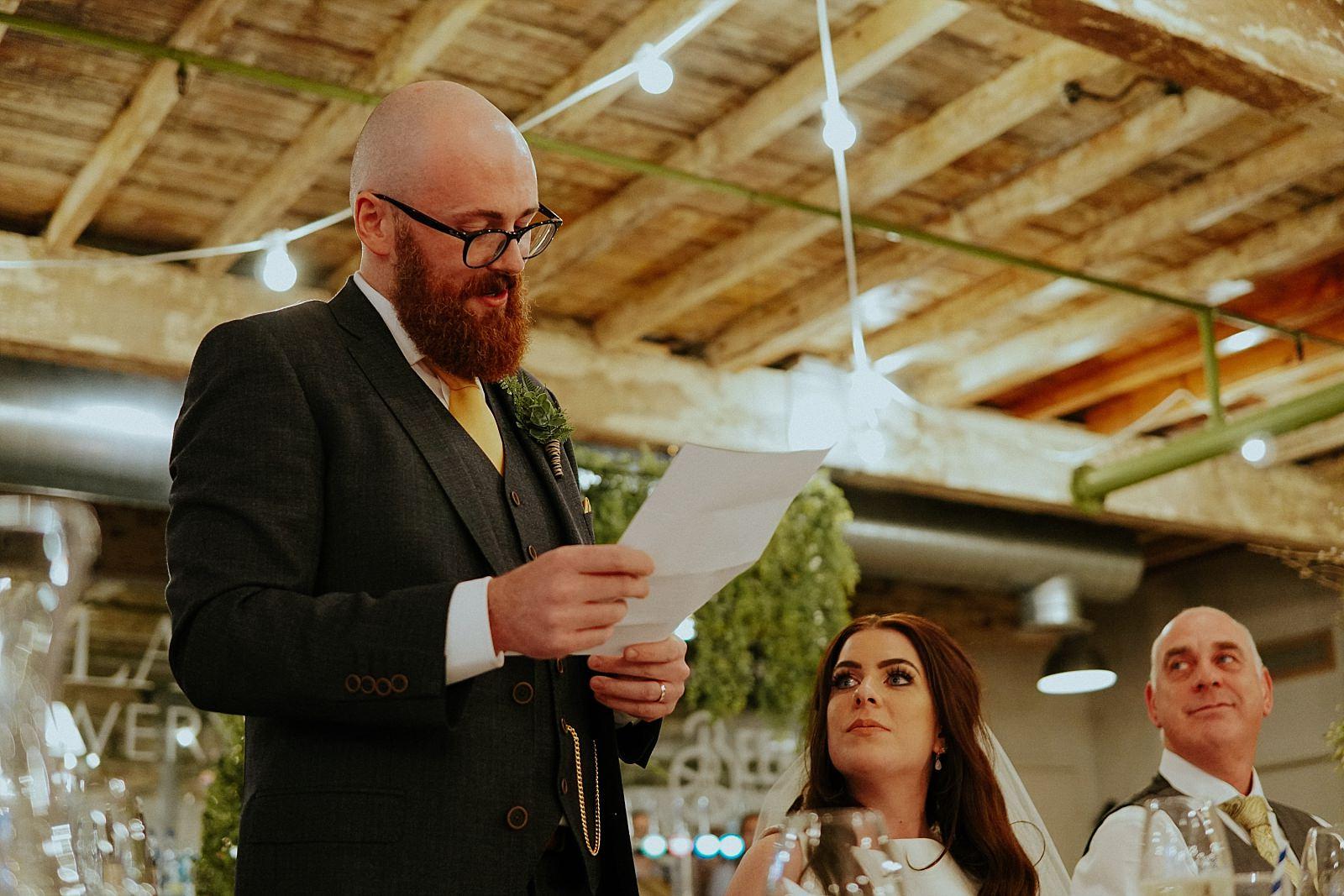 groom reading his speech to his bride